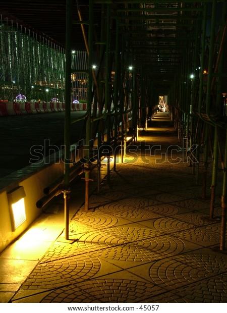 Lit pavement at night at a bridge under construction