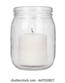 A lit pillar candle in a glass jar isolated on a white background