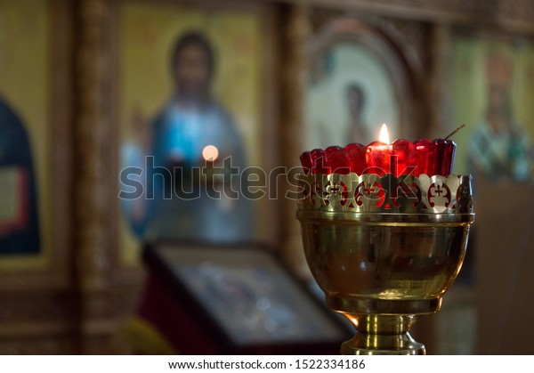 Lit red lamp in front of the icons in a shiny Golden candlestick on a blurred background. Orthodox church.