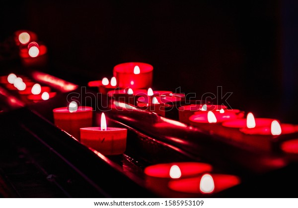 Lit red votive candles in a church in Portugal