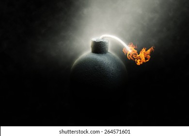 Lit round black bomb with a burning fuse counting down to detonation illuminated in a shaft light shining through the darkness, conceptual image