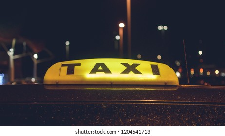 Lit Up Taxi Sign, On Vehicle Roof after Rain, Night Photography Shallow Depth of Field
