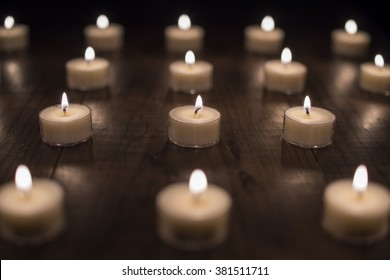 Lit Tea Light Candles on Wooden Table (Center Focus)
