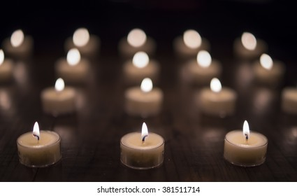 Lit Tea Light Candles on Wooden Table (Front Focus)