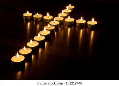 Lit tea lights in the shape of a cross on a polished wooden surface.