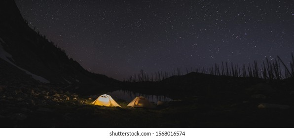 Lit tent at night in the Sawtooth Mountains of Idaho with stars in the sky above next to an alpine lake