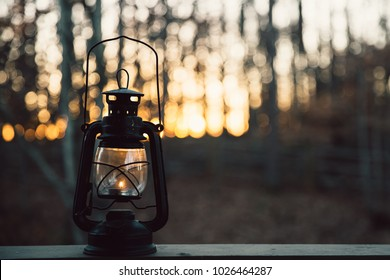 Lit vintage lantern against blurred sunset background
