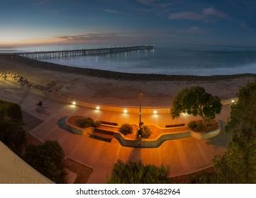 Lit walking path with Ventura pier in background.