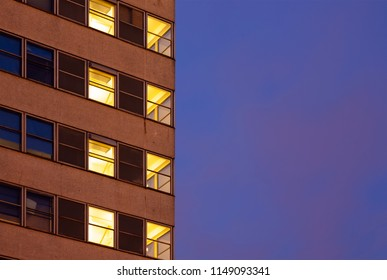 Lit windows of an office building and blue evening sky