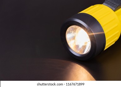 Lit yellow flashlight