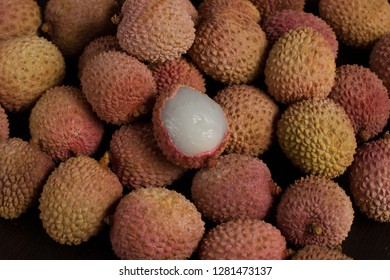 Litchi poured on a dark background. One peeled