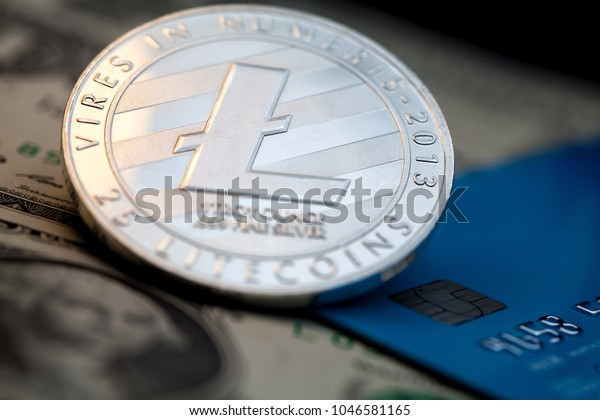 Litecoin cryptocurrency silver token with a blue credit card and US dollar cash paper money