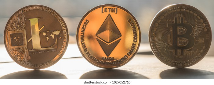 Litecoin, ethereum and bitcoin cryptocurrency on wooden table top in the morning light