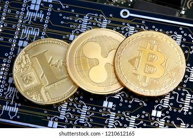 Litecoin, Ripple & Bitcoin golden coins representing cryptocurrenies.
