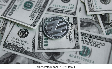 Litecoins crypto currebcy on US dollars. Digital currency close-up. Virtual money. Metal coins of Litecoins on banknotes of one hundred dollars. Exchange. Bussiness, commercial.