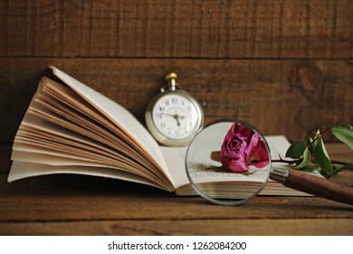 Literary still life with book, clock, magnifying glass and withered rose