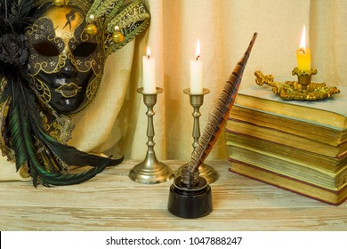 Literature concept, candle in a candlestick, near a Venetian mask and an inkwell with a pen, books on a background of bright material