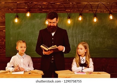 literature. literature lesson for two small girls with serious teacher man. literature and grammar. school lesson of literature subject. interesting.