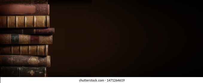 literature / reading concept: banner or header image with stack of antique leather bound books against a dark background - Shutterstock ID 1471264619