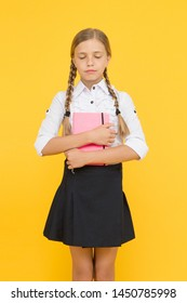 Literature for school. Adorable little girl with closed eyes holding book of English literature on yellow background. Cute small child enjoying childrens literature. Preparing for a literature exam.