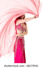 Lithe adult caucasian belly dancer with red hair and pink belly dancing outfit performing a dance with veils on a white background. Not Isolated