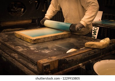 Lithography profession. Guy applying color on the stone.