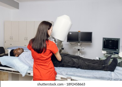 Lithotripsy for kidney and ureteral stones. Back view of woman doctor, using ultrasound scan to determine the stone position before the lithotripsy. Modern lithotripter to break up kidney stones