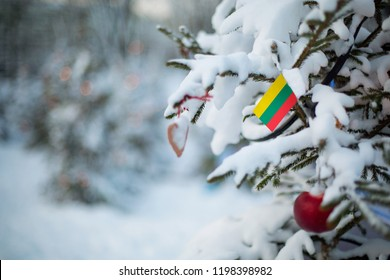 Lithuania flag. Christmas background outdoor. Christmas tree covered with snow and decorations and Lithuanian flag. New Year / Christmas holiday greeting card.
