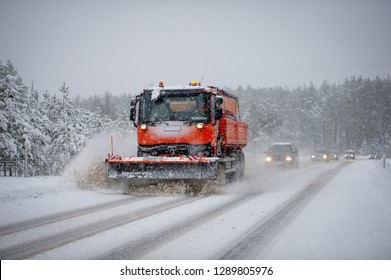 LITHUANIA - JANUARY 20, 2019: Snow plough truck clearing road during heavy snowstorm. A snowplow is a device intended for mounting on a vehicle, used for removing snow and ice from outdoor surfaces.