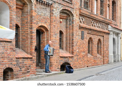 Lithuania, Vilnius - July 2019. Street musician plays accordion on Vilnius street. Performance of street musician. Musician with accordion playing in the street with red bricks building on background