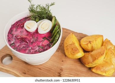 Lithuanian cold beet soup (Saltibarsciai). Placed on wooden board, served with baked potatoes