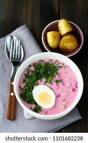 Lithuanian Saltibarsciai (Cold Beet Soup) with a hard boiled egg and new potatoes on a wooden background