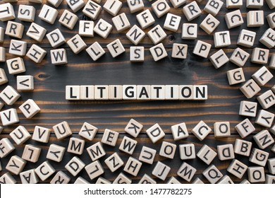 litigation - word from wooden blocks with letters, the process  determining issues a court Arbitration and Litigation concept, random letters around, top view on wooden background