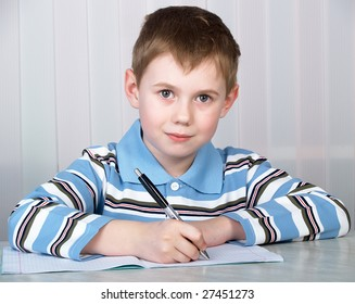 the litle boy doing homework on the table