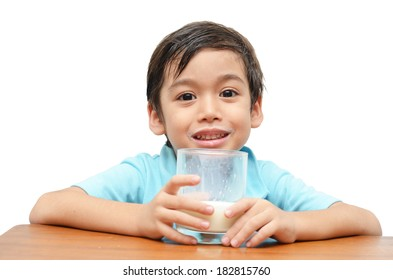 Litlle boy holds a glass of fresh milk