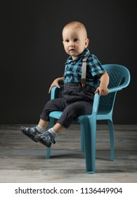 litlle boy siting on plastic chair