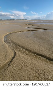 Litlle river flowing on the beach into sea, Somme Bay, Picardy, France.