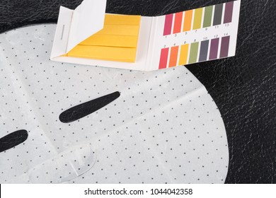 Litmus paper and facial sheet mask. Test the pH value of the mask.