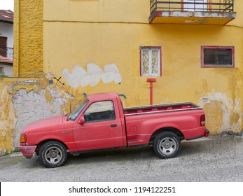 LITOCHORO, GREECE -  JULY 24. 2018,Old vintage red Ford ranger  pickup truck  in front of old yellow house, Litochoro July  24. 2018. Olympus region, Macedonia, Greece