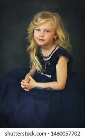 litte girl in navy blue dress over dark background