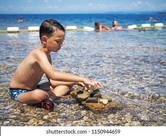 Littel boy playing in water with stones