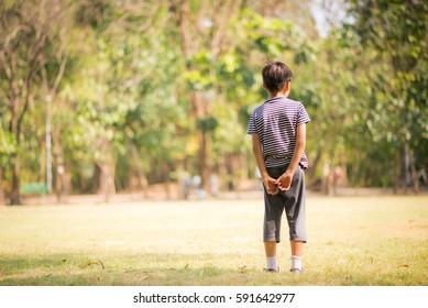 Littel boy standing alone in the park
