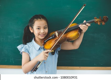 A littel cute girl playing violin on music class room at school