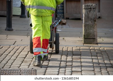 litter collector working for the local council walks along street with barrow for collecting rubbish