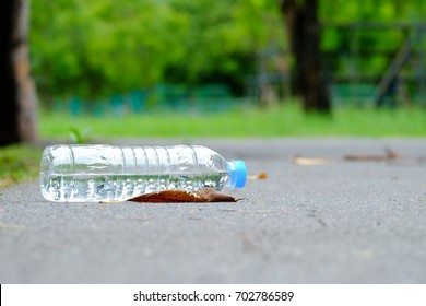 Littering plastic bottle with drinking water on the road at the green park