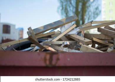 a litterless metal container without a cover is full of construction debris and waste standing in the middle of the street next to a building under construction in the city in the sun