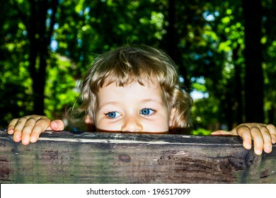 Little 3 year old girl peek over the wooden bars.