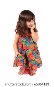 Little 3 year old girl sitting on a small stool holding her hand to her face with a wondering look on a white background