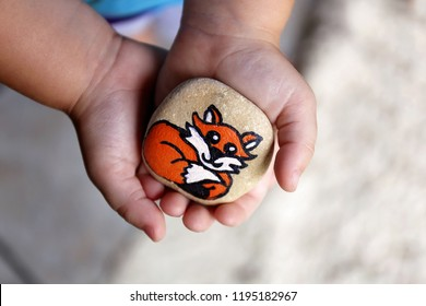 A little 3 year old toddler child's hands are gently holding a painted rock with a fox on it, that they will hide in the garden.