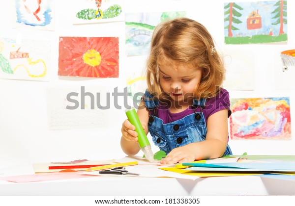 Little 3 years old blond girl gluing color cardboard with glue stick